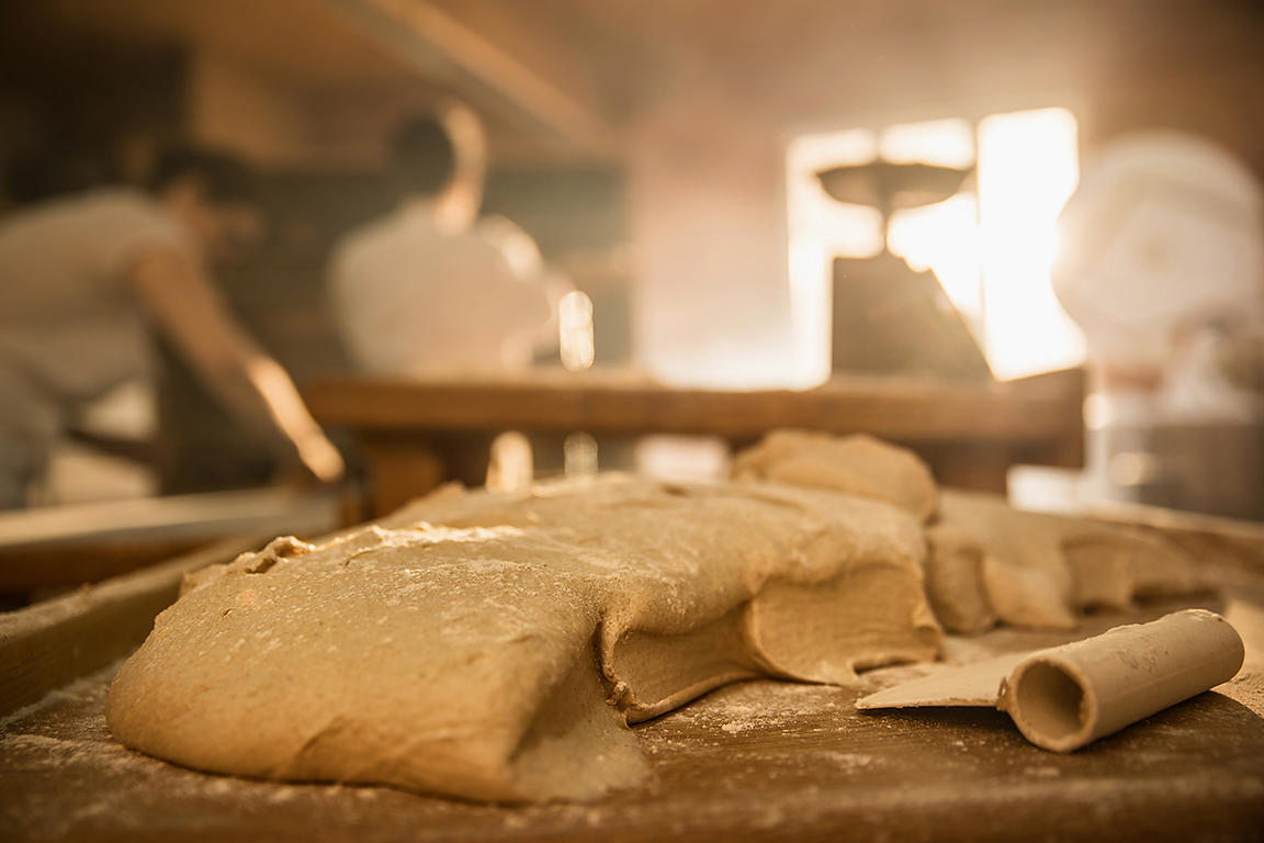in an artisan bakery, close-up of bread dough. In the background the bakers work while the morning sun comes in through the window..