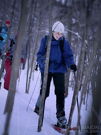 Woman snowshoeing in forest
