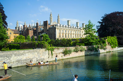 Punts and passengers glide past Clare College (founded 1326) on the  River Cam past the Garret Hostel bridge. Cambridge, United Kingdom