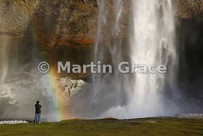 Seljalandsfoss waterfall in late winter with tourist photographing, Iceland south coast