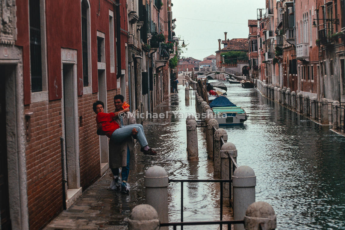 A man carries his spouse during the acqua alta. Venice, Italy, October, 1993.