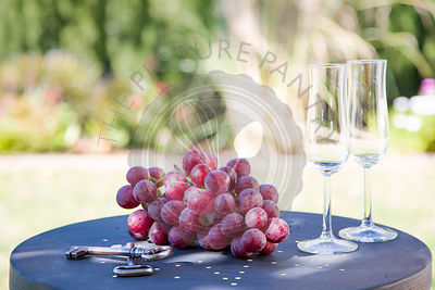 Red grapes on metal table ,with champagne glasses and keys in summer garden.