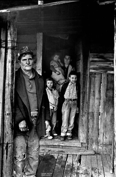 Miner on porch with family in doorway, Wilder, TN
