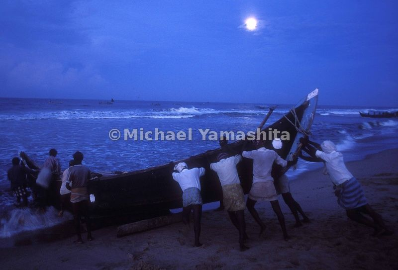 Under a full moon, fishermen prepare their boat for the night-time laying of the nets.