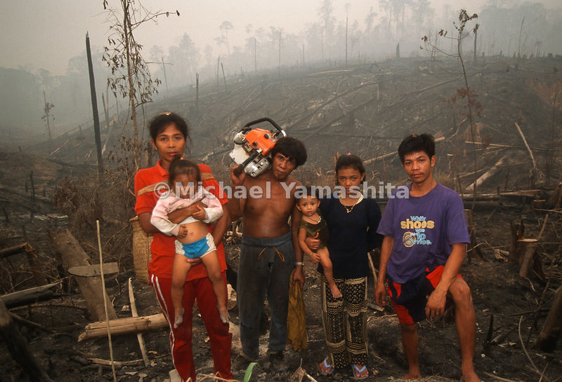 A family poses in front of a forest destroyed by Indonesia's Plague of Fire.