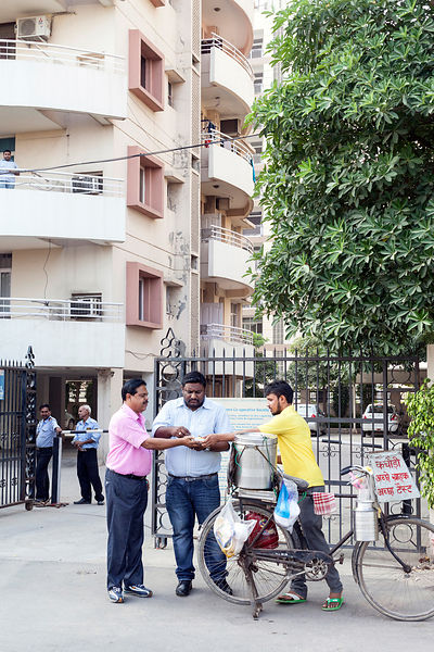 India - Gurgaon - Two residents buy kachori from a vendor outside their gated community,