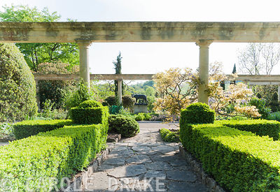 Colonnade on the Great Terrace framing bronze Wolf with Romulus and Remus. Iford Manor, Bradford-on-Avon, Wiltshire
