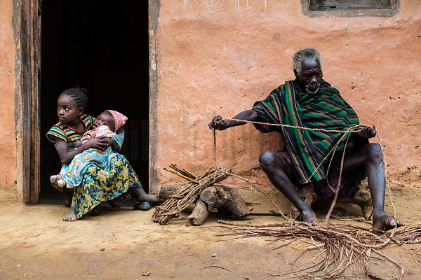 Elderly Man Weaving Rope from Strips of Tree Bark