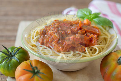 Bowl of spaghetti with vegetarian tomato bolognese sauce on wooden board and fresh Raf tomatoes.