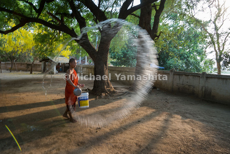 A monk sprays water over a dusty courtyard at Bagan's ancient Lawkananda Pagoda. Dampening the soil reduces the dust stirred up by footsteps.