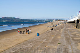 Group of people walking dogs on Aberavon Beach, Port Talbot, South Wales.