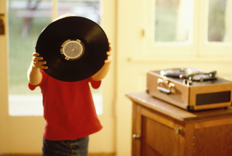 boy holds LP record in front of face