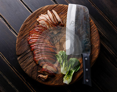 Sliced Peking Duck and cleaver on cutting board on black wooden background