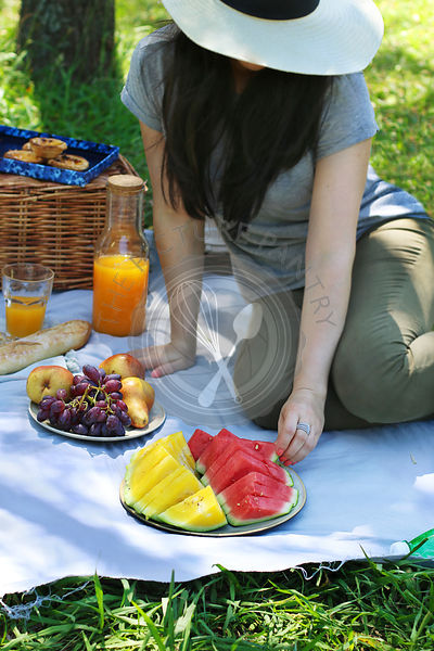 Young female enjoying outdoor picnic In the park.Woman sitting on the blanket and eating watermelon