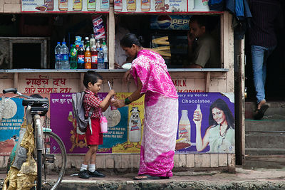 A woman helps her son with a drink at a market near Sassoon Docks, Mumbai, India.