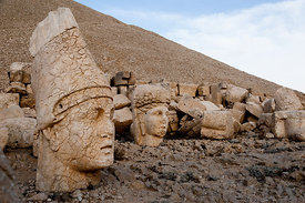 The west terrace of Mount Nemrut with heads of the colossal statues and the tumulus.  Head of Antiochos I in foreground with Commagene behind.  The UNESCO World Heritage Site at Mount Nemrut where King Antiochus of Commagene is reputedly entombed.   (Turkish: Nemrut Dağı)