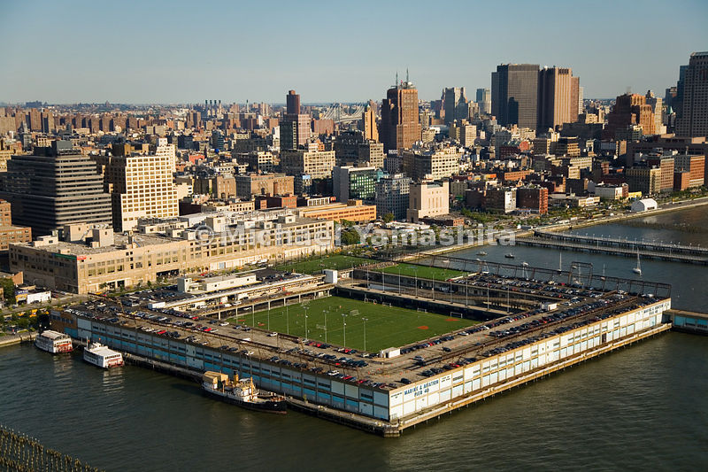 Pier 40, at West Houston Street and the Hudson River, houses the Pier Park and Playground Association, as well as fields for soccer, baseball, football, rugby, and lacrosse.  The athletes share space with a long-term parking garage.  Manhattan, New York City.