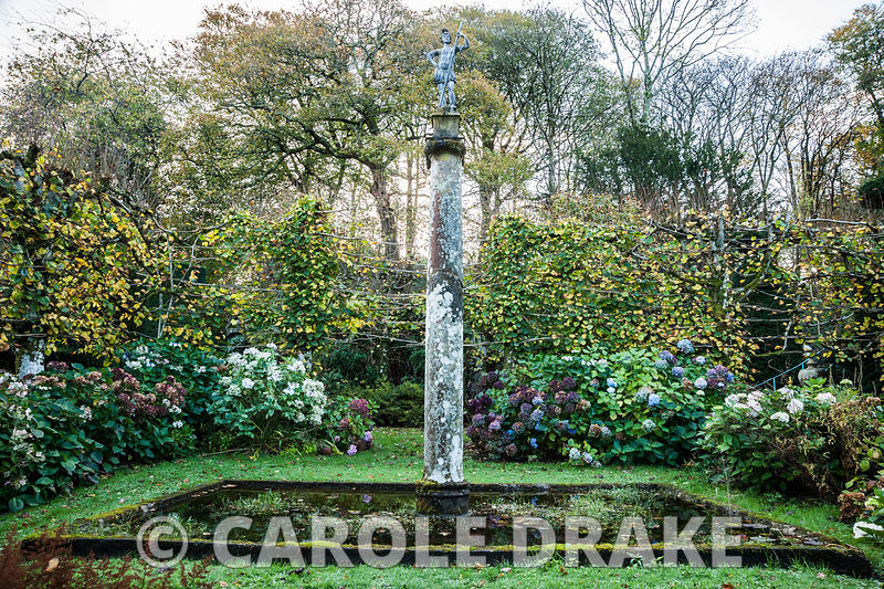 Sunken garden surrounded by pleached limes, hydrangeas and with square central pool containing column with statue on its top. Plas Brondanw, Penrhyndeudraeth, Gwynedd, Wales