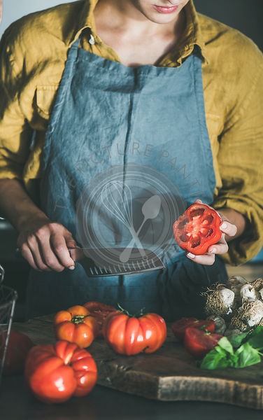 Woman cooking tomato sauce or pasta at kitchen counter