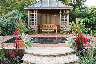 Summerhouse with reflecting pool surrounded by brightly coloured perennials including Lobelia cardinalis, cleomes, plectranthus and aconites. Crab Cottage, Shalfleet, Isle of Wight, UK