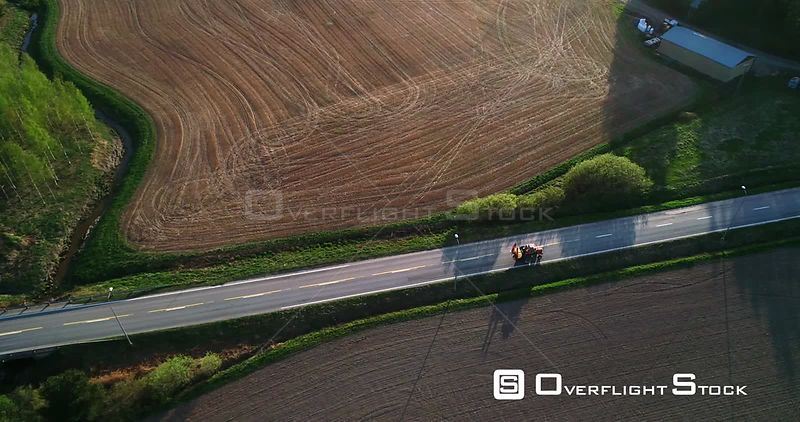 Tractor on the Road, Aerial View Following a Fertilizer Machine Leaving the Field and Driving on a Asphalt Route, on a Sunny Spring Evening Dawn, in Kemio, Varsinaissuomi, Finland