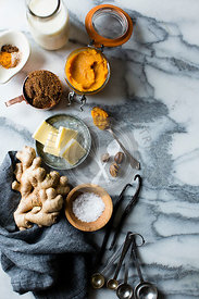 Cookery ingredients on marble work surface. Butter, ginger, milk, spices.