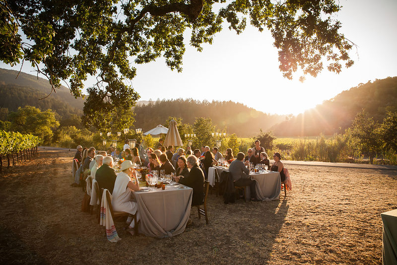 "Dining al fresco among the vines and setting sun at Inglenook's private party. Photo by <a href=""http://www.tinacciphoto.com"">Jason Tinacci</a>"