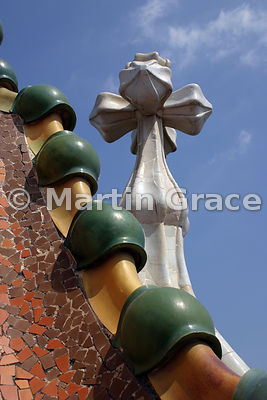 Roof-line of Gaudi-designed Casa Batllo in Barcelona, showing ceramic spheres on ridge, glass & ceramic mosaic, 4-armed cross
