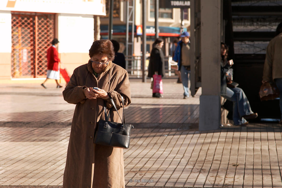 A woman using a cell phone on the street in Santiago, Chile.