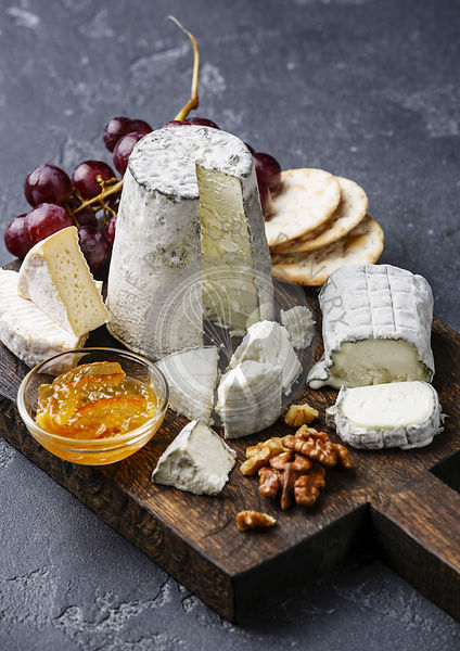 Goats Cheese board Snack assortment with confiture and grape on cutting board on black background