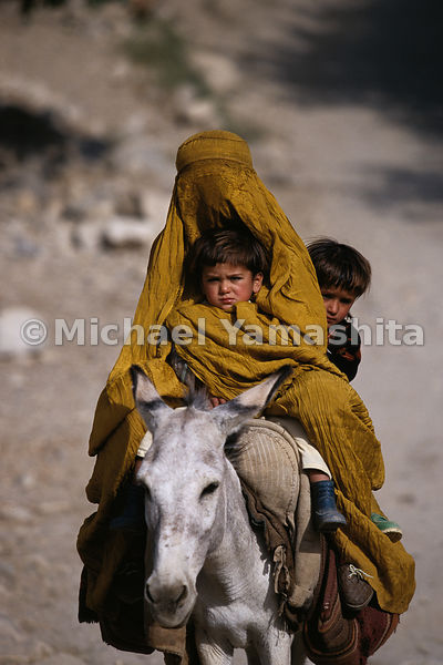 Time seems to have stopped in many parts of Afghanistan, where often the best mode of transportation is donkey-back, just as it would have been in Marco Polo's day. A woman completely covered by her silk burkha, takes her children to a doctor.  Feyzabad, Afghanistan
