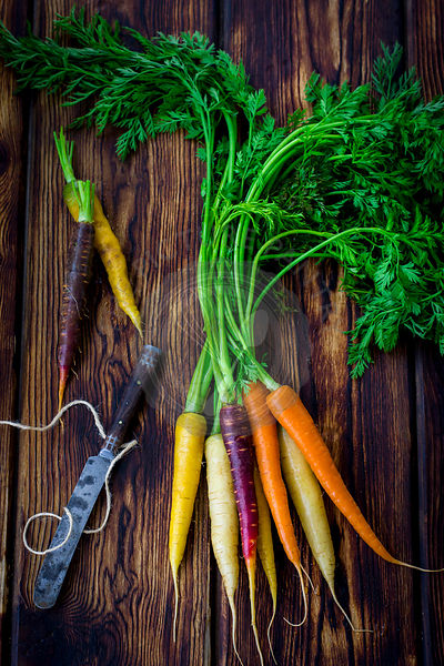 Rainbow carrots with knife and twine on dark wood table