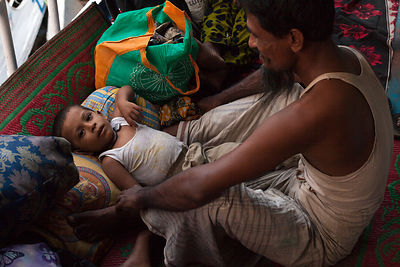 Bangladesh - Dhaka - A man waits with his infant son on board deck of a passenger ferry at Sadarghat