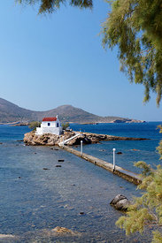 Aghios Isidhoros church set on a small Islet joined to the mainland by a narrow causway, Leros, Dodecanese Islands, Greece.