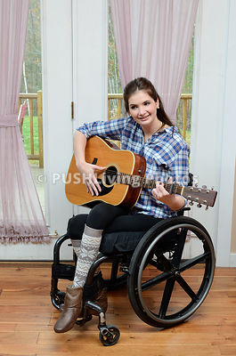 Young woman using a wheelchair listening to and playing music