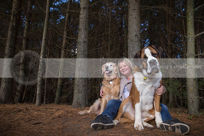 two big dogs sitting with owner in pine tree forest showing family bond