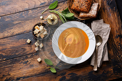 Pumpkin soup with sage and Croutons on wooden background Copy space
