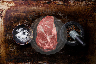 Raw fresh marbled meat Steak Rib eye Black Angus and seasoning on dark metal background
