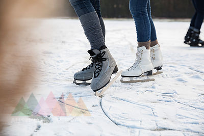 Feet of ice skating people on frozen lake