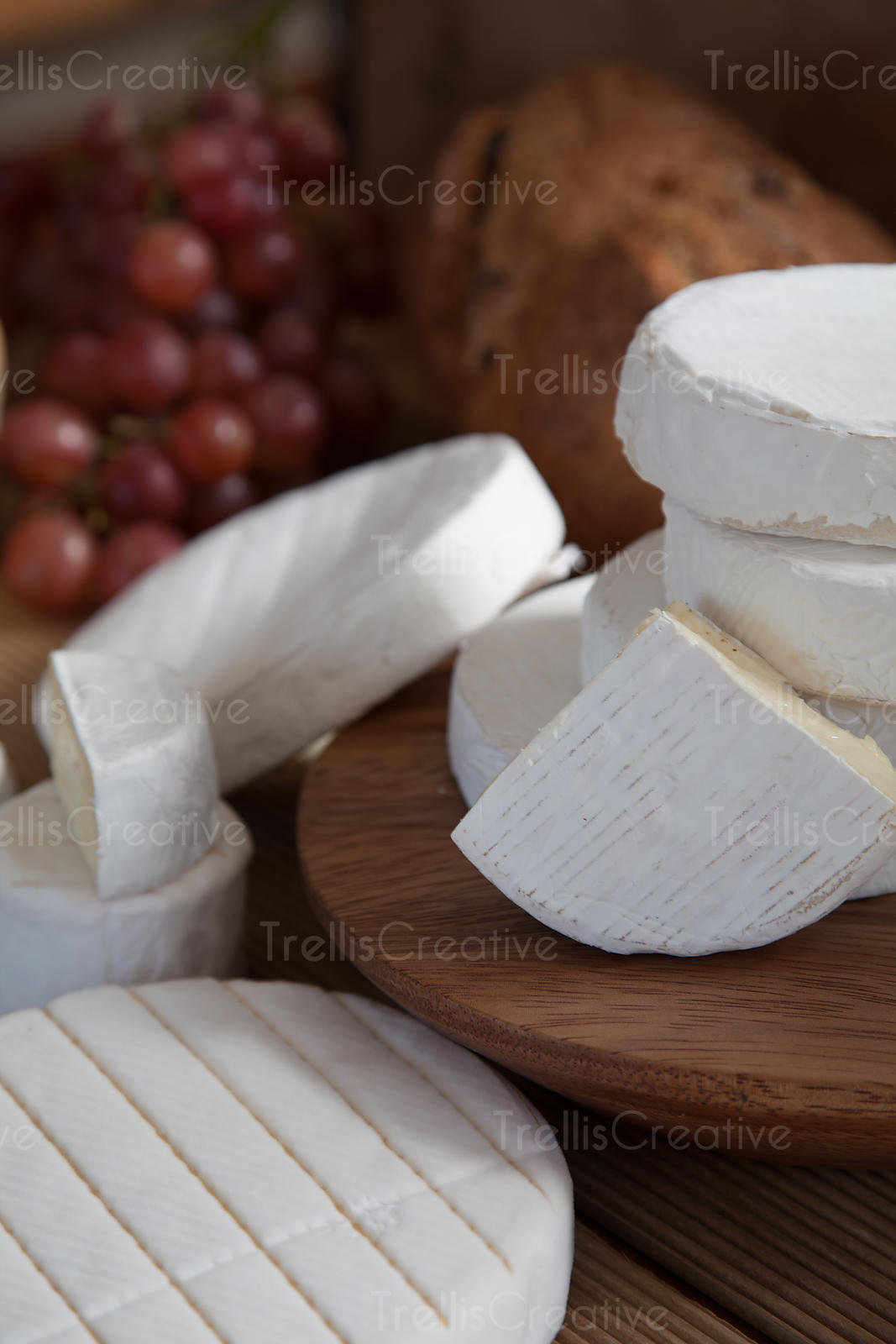 Stacks of brie cheese wheels and wedges on a wooden board with grapes and bread