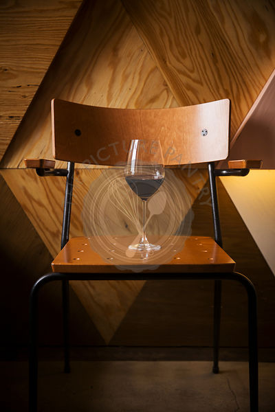 Glass of red wine standing on vintage chair