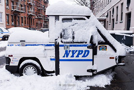 Snow covered NYPD three-wheeler parked on the street in Chelsea, NY.