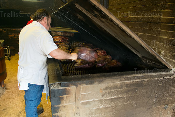 chef handling meat on a smoker