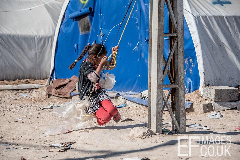 A Little Girl Resident Of The Hamam al Alil IDP Camp Near Mosul Plays On A Rope Swing Made From Electrical Cable And Plastic Bags