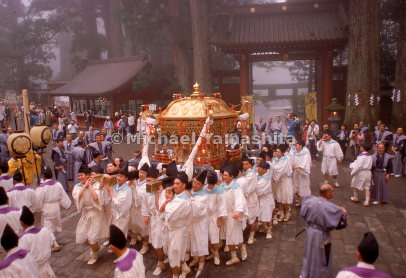 White-clad festival participants carry a golden omikoshi (god platform), Japan.