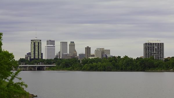 Wide Shot: A Sunset With a Thick & Low Cloud Deck Over a Gold Lit Tulsa Skyline & Arkansas River (Day To Night)
