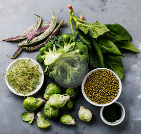 Healthy Green food Clean eating selection Protein source for vegetarians: brussels sprouts, broccoli, spinach, spirulina on gray concrete background