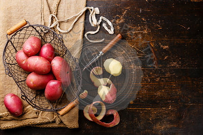 Raw peel potato in metal basket and burlap bag on wooden background copy space