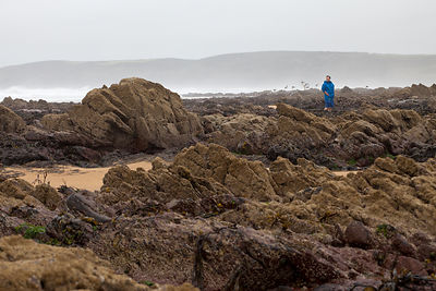 UK - Pembroke - Jonathan Williams, owner of the award winning Cafe Mor that promotes cooking with seaweed, stands amongst the rocks and water pools on Freshwater West Beach, where he collects most of his ingredients.