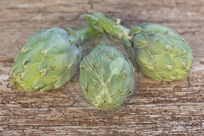Three whole artichokes on rustic wood table